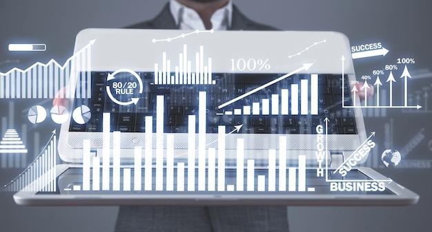 Uomo d'affari che tiene il computer portatile con grafici di crescita. attività commerciale. sviluppo. successo