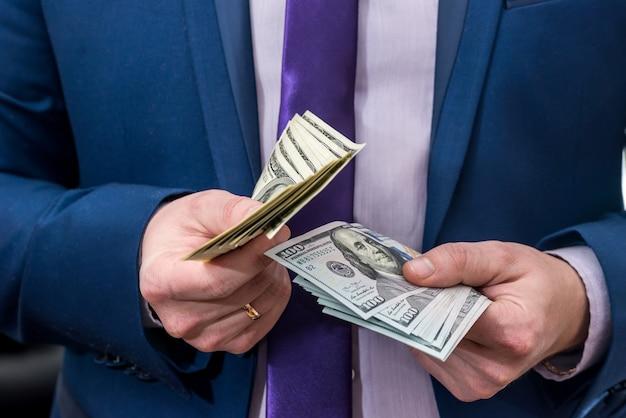 Uomo d'affari che tiene una grande quantità di dollari e ti dà