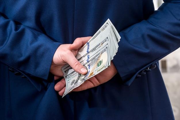 Uomo d'affari che tiene grande quantità di dollaro