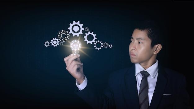 Uomo d'affari che tiene lampadina con un'icona a forma di ingranaggio. l'idea di â€â€ispirazione tecnologica online. concetto di idea di innovazione.