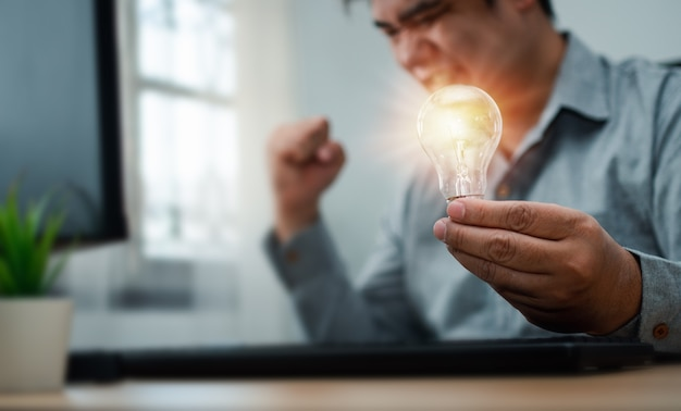 Uomo d'affari che tiene la lampadina e si sente felice ed entusiasta di nuove innovazioni e idee per pannelli aziendali di successo