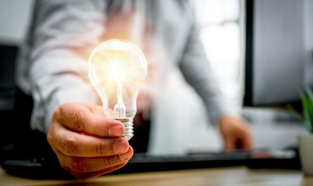 Uomo d'affari che tiene lampadina e si sente felice di nuove innovazioni e idee per pannelli aziendali di successo. concetto di innovazione di idee tecnologiche creative per soluzioni aziendali