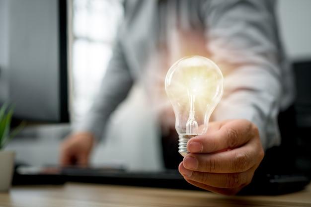 Uomo d'affari che tiene la lampadina e si sente felice di nuove innovazioni e idee per pannelli aziendali di successo.