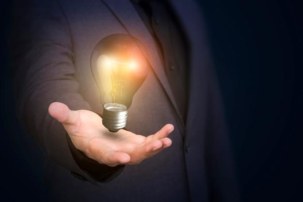 Lampadina della tenuta dell'uomo d'affari di nuove idee e creatività