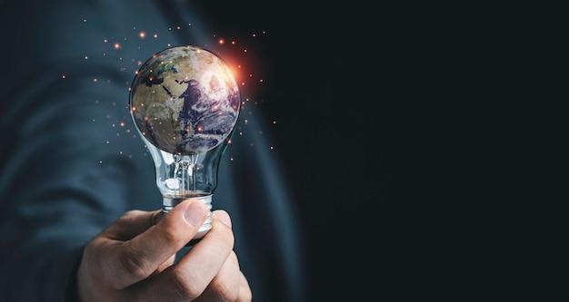 Uomo d'affari che tiene la lampadina con la terra per la giornata della terra e il concetto di ambiente di risparmio energetico, elemento di questa immagine della nasa e rendering 3d.