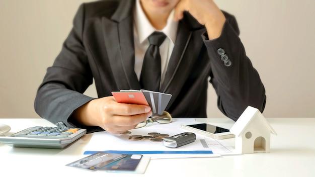 Uomo d'affari che tiene molte carte di credito e gesto stressante dal concetto di finanziamento dei debiti e carta di credito credit