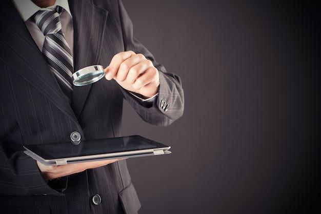 Uomo d'affari che tiene lente d'ingrandimento e concetto di tavoletta digitale tablet