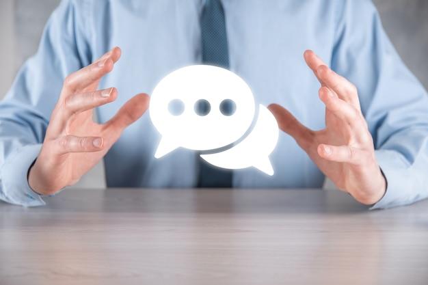 Uomo d'affari che tiene un'icona del messaggio, segno di notifica di conversazione della bolla nelle sue mani. icona chat, icona sms, icona commenti, fumetti