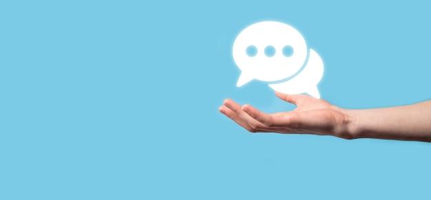 Uomo d'affari che tiene un'icona del messaggio, segno di notifica di conversazione della bolla nelle sue mani. icona chat, icona sms, icona commenti, fumetti.