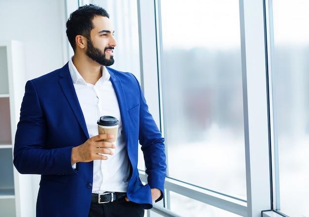 Telefono cellulare e tazza di caffè della tenuta dell'uomo d'affari negli edifici per uffici