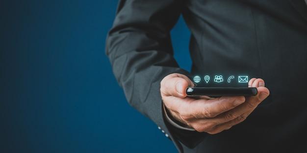 Uomo d'affari che tiene il telefono cellulare con icone di contatto e comunicazione incandescente sopra di esso
