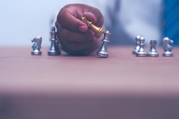 Uomo d'affari che tiene e si muove la figura degli scacchi nel successo della competizione
