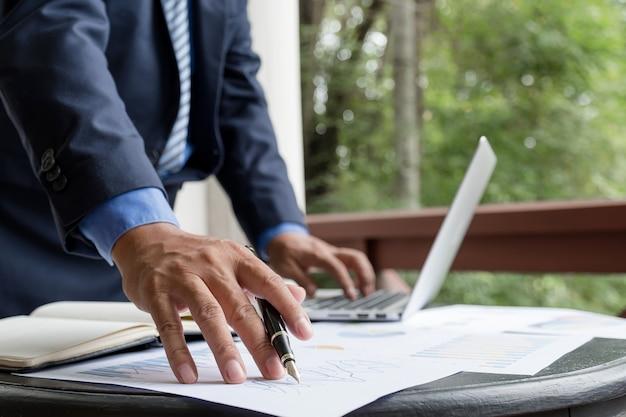 Grafico di analisi della penna della tenuta dell'uomo d'affari con il computer portatile all'ufficio domestico per l'impostazione degli obiettivi aziendali