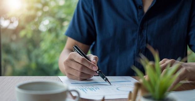 Uomo d'affari che tiene la penna e indica il riepilogo del grafico cartaceo analizzando il rapporto annuale di attività con l'utilizzo del computer portatile alla scrivania dell'ufficio della stanza.