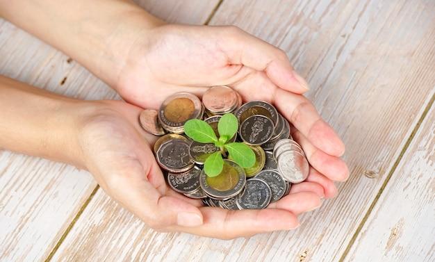 Uomo d'affari che tiene pianta che germoglia da una manciata di monete finanziare il concetto di business background