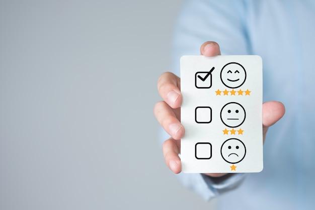 Uomo d'affari che tiene scheda di valutazione di prodotti e servizi. concetto di soddisfazione del cliente.