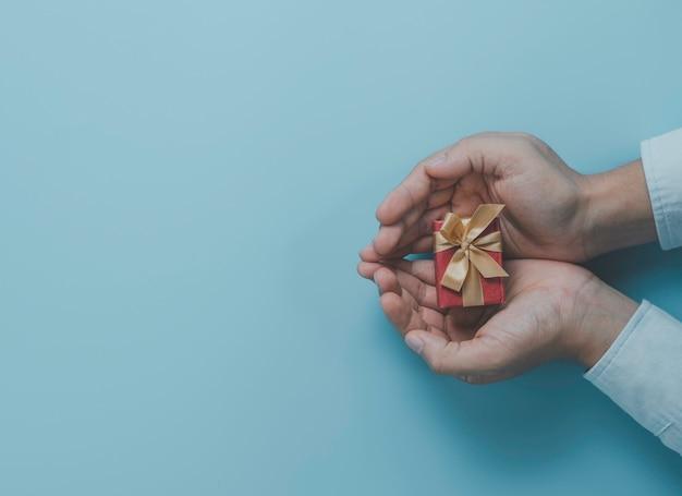 Uomo d'affari che tiene confezione regalo rossa con nastro d'oro per dare presente all'amante, buon natale, felice anno nuovo e concetto di san valentino.