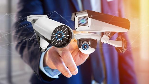 Uomo d'affari che tiene un sistema di videocamera di sicurezza e una connessione di rete - rappresentazione 3d