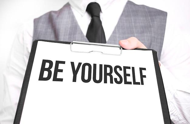 Uomo d'affari che tiene foglio di carta con un messaggio sii te stesso