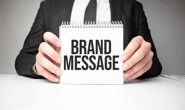 Uomo d'affari che tiene in mano un foglio di carta con un messaggio messaggio del marchio