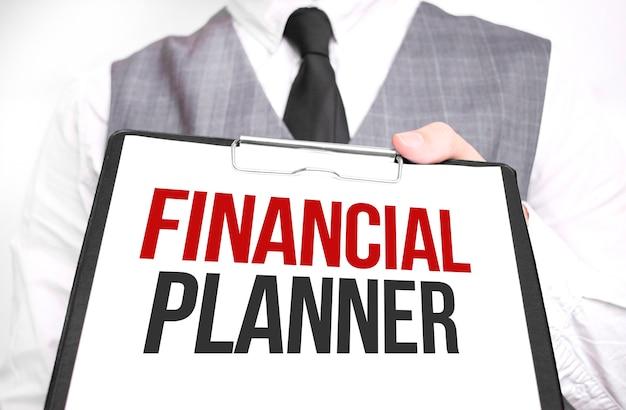 Uomo d'affari che tiene foglio di carta con un messaggio pianificatore finanziario