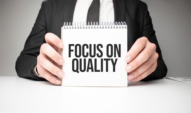 Uomo d'affari che tiene un foglio di carta con un messaggio focus sulla qualità