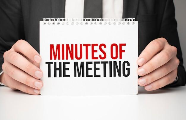 Uomo d'affari che tiene un foglio di carta con un messaggio minuti della riunione