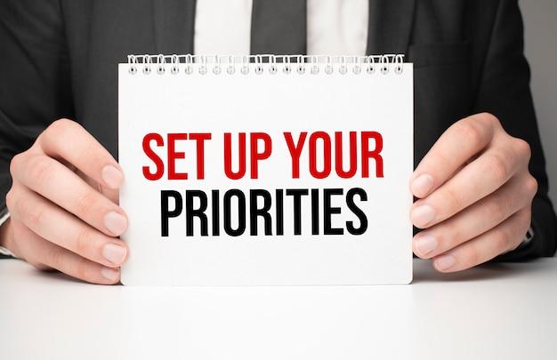 Uomo d'affari che tiene un foglio di carta con un messaggio imposta le tue priorità