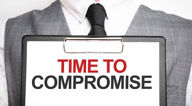 Uomo d'affari che tiene foglio di carta con un messaggio tempo di compromesso