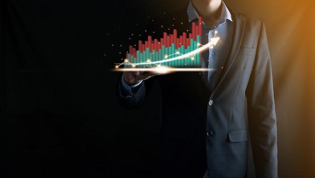 Uomo d'affari che tiene e mostra un ologramma virtuale crescente di statistiche, grafico e grafico con freccia su su sfondo scuro. mercato azionario. crescita aziendale, pianificazione e concetto di strategia.