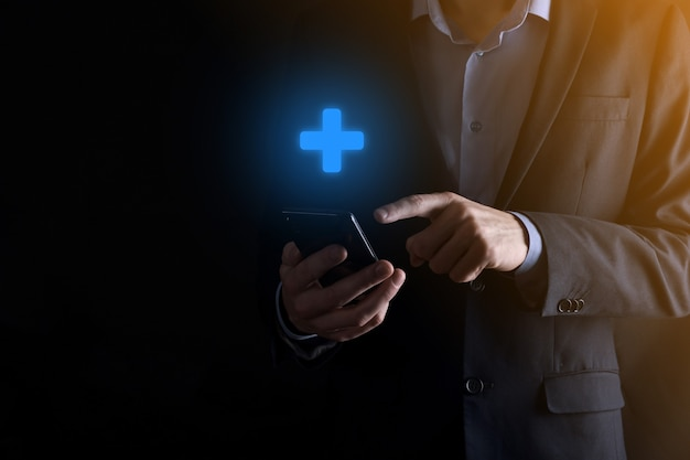 Uomo d'affari che tiene smartphone e croce blu