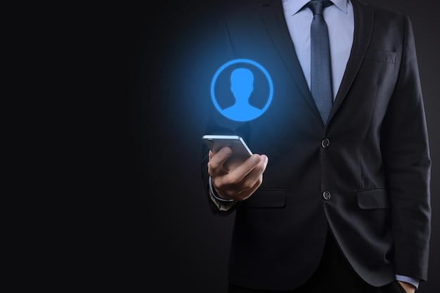Uomo d'affari che tiene smartphone con avatar olografico