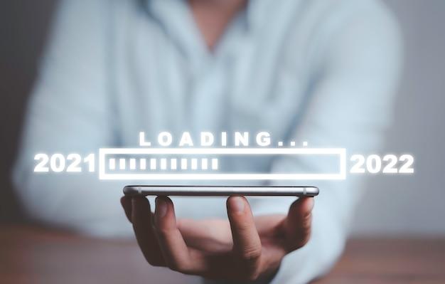 Uomo d'affari che tiene smartphone con barra di avanzamento del caricamento per la vigilia di capodanno e cambio di anno dal 2021 al 2022.
