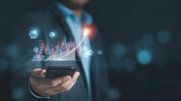 Uomo d'affari che tiene smartphone con grafico tecnico virtuale e grafico per analisi del mercato azionario, investimento tecnologico e concetto di investimento di valore.