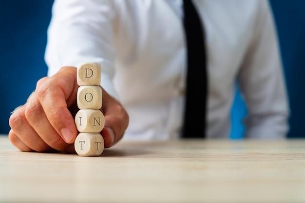 Uomo d'affari che tiene una pila di dadi di legno che trasportano un segno di non girarsi per farlo firmare