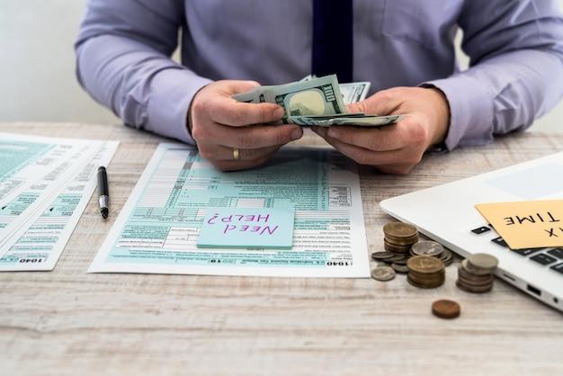 Uomo d'affari che tiene adesivo con iscrizione hai bisogno di aiuto per compilare il modulo fiscale usa 1040 e contare i soldi. modulo fiscale noi ufficio reddito aziendale concetto di riempimento a mano