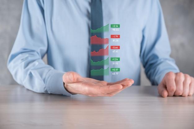 Uomo d'affari che tiene tablet e analisi del mercato azionario, cambio valuta e operazioni bancarie, che mostra un ologramma virtuale in crescita di statistiche, grafici e grafici, crescita aziendale, pianificazione e concetto di strategia