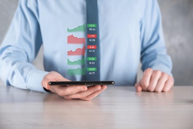 Uomo d'affari che tiene tablet e analisi del mercato azionario, cambio valuta e operazioni bancarie, mostrando un ologramma virtuale in crescita di statistiche, grafici e grafici, crescita aziendale, pianificazione e concetto di strategia.