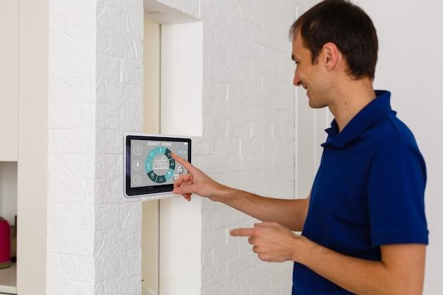 Uomo d'affari che tiene un computer tablet con sistema intelligente casa