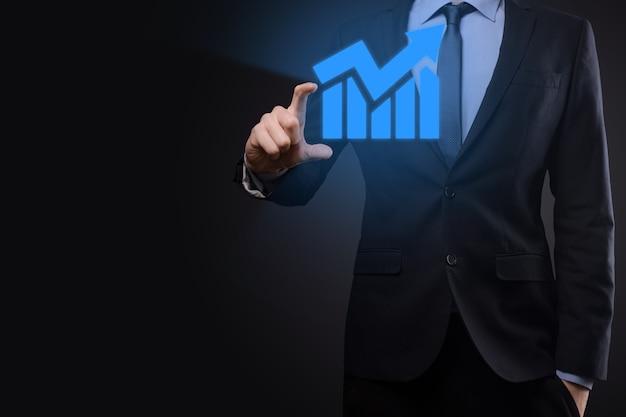Uomo d'affari che tiene tablet e mostra un ologramma virtuale in crescita di statistiche, grafico e grafico con freccia su su sfondo scuro. mercato azionario. crescita aziendale, pianificazione e concetto di strategia.