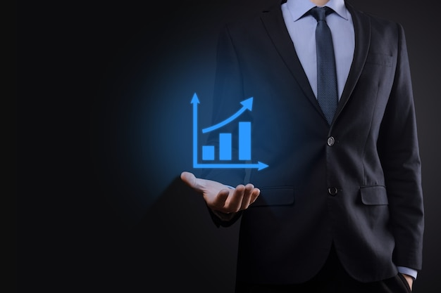 Imprenditore tenendo tablet e mostrando un crescente ologramma virtuale di statistiche, grafico e grafico con freccia su su sfondo scuro.