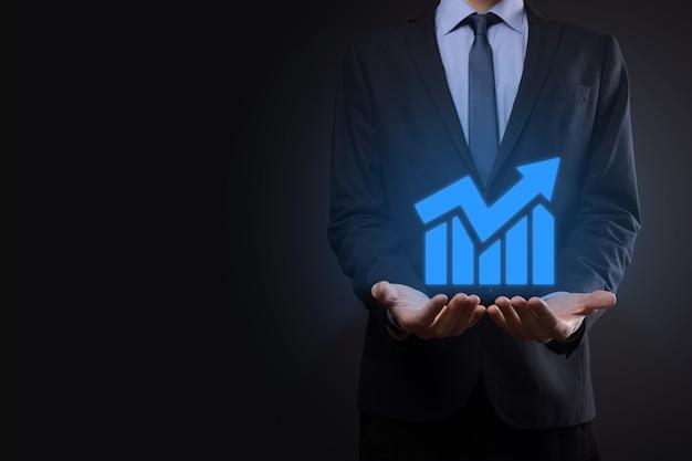 Uomo d'affari che tiene compressa e mostra un ologramma virtuale crescente di statistiche, grafico e grafico con freccia in alto sulla parete scura. mercato azionario. crescita aziendale, pianificazione e concetto di strategia.