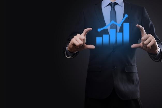 Uomo d'affari che tiene compressa e mostra un ologramma virtuale crescente di statistiche, grafico e grafico con freccia in alto sulla parete scura.