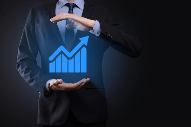 Imprenditore tenendo tablet e mostrando un crescente ologramma virtuale di statistiche, grafico e grafico con freccia in alto