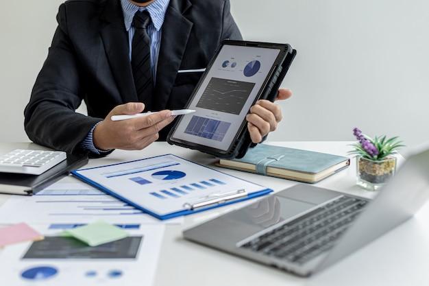 Uomo d'affari in possesso di un tablet che mostra i dati di vendita di un venditore, sta incontrando il responsabile delle vendite per pianificare la gestione della crescita delle vendite, piano di marketing per aumentare le vendite. concetto di gestione delle vendite.