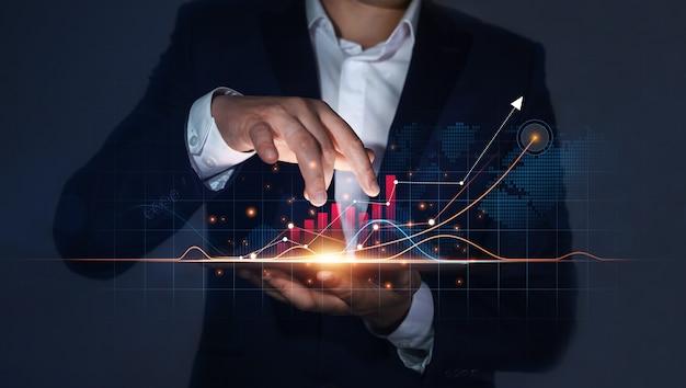 Imprenditore in possesso di tablet con crescente ologramma virtuale di statistiche grafico e grafico