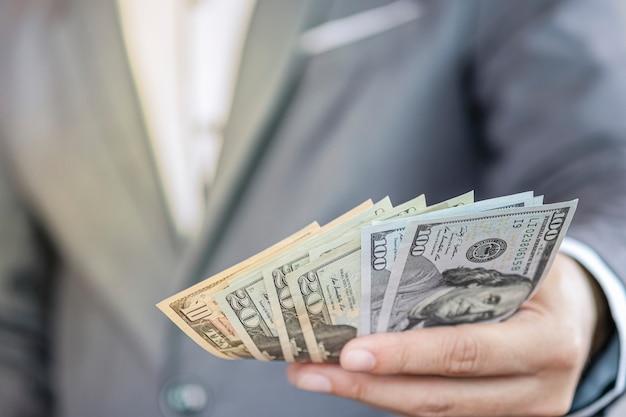 Uomo d'affari che tiene la banconota usd per il pagamento. il dollaro usa è la valuta di scambio principale e popolare nel mondo. concetto di investimento e risparmio.