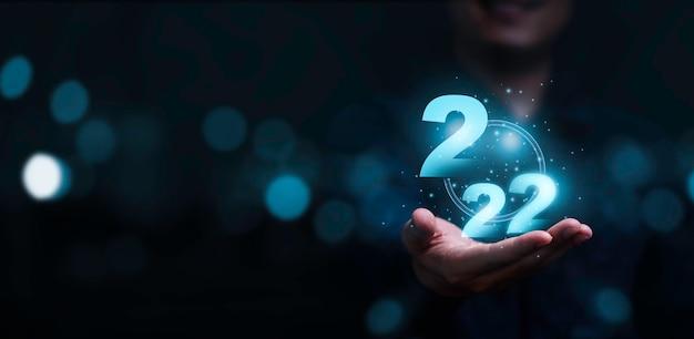 Uomo d'affari che tiene numero 2022 virtuale con sfondo blu bokeh e copia spazio per il concetto di buon natale e felice anno nuovo.
