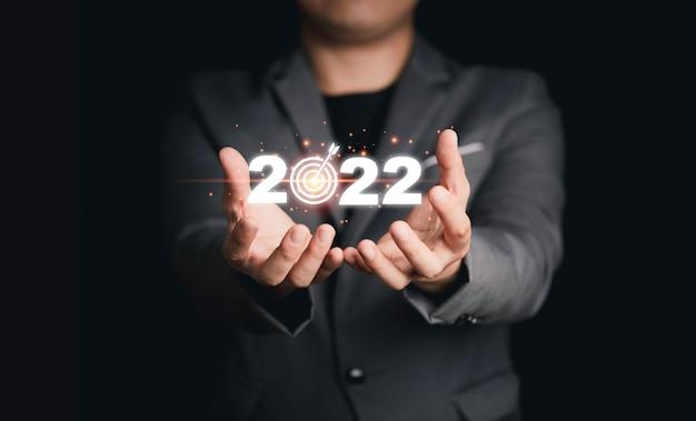 Uomo d'affari che tiene 2022 virtuale con la scheda di destinazione per l'obiettivo dell'obiettivo aziendale di installazione per l'inizio del nuovo anno.