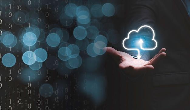 Uomo d'affari che tiene il cloud computing virtuale a portata di mano per trasferire le informazioni sui dati e caricare l'applicazione di download. concetto di trasformazione tecnologica.